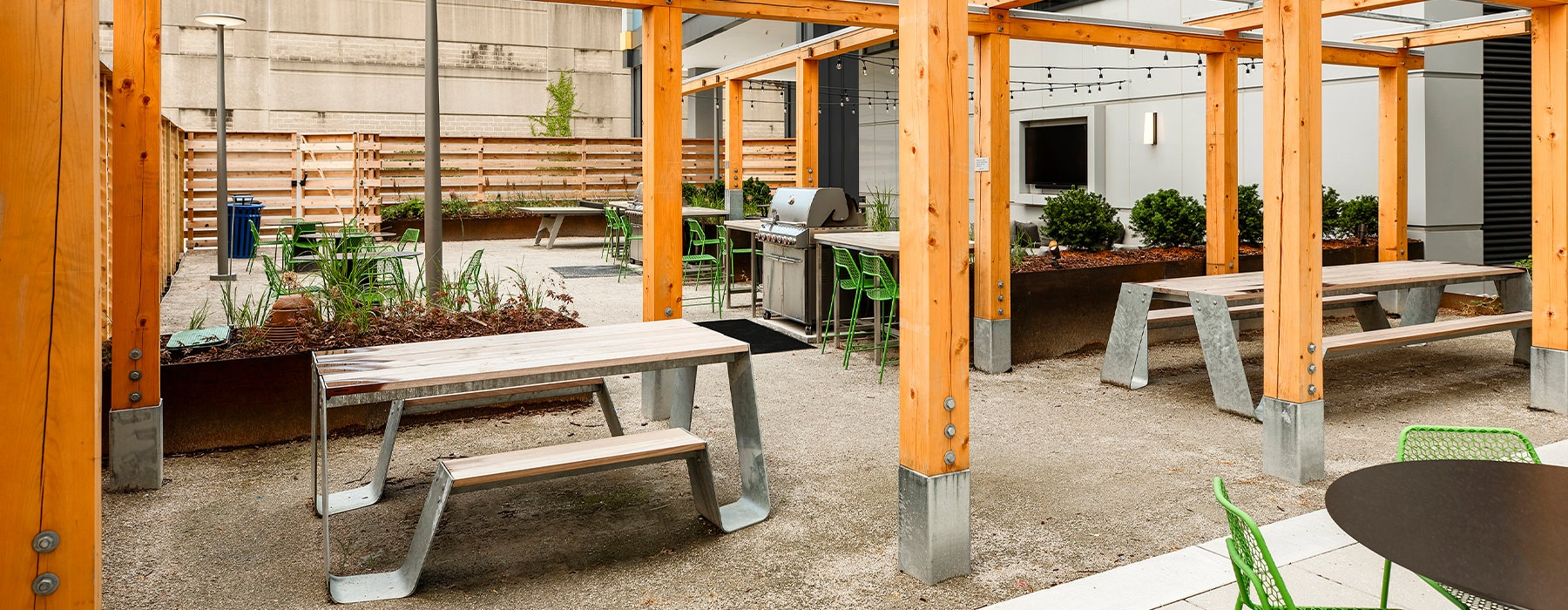 Outdoor community space with tables and a grill